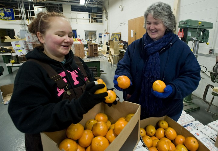 Lexus Ryman, 17, of Edinburg, left, a student at Central High School, and her teacher Sherry Heishman, right,  sort through fruit orders that arrived at the school on Monday for their fundraiser for the agriculture department. Heishman received  the national FFA agriscience teacher of the year award last month. Rich Cooley/Daily